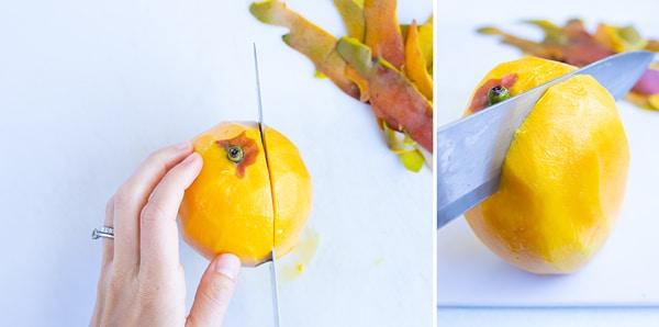 Cutting a peeled mango with a knife.