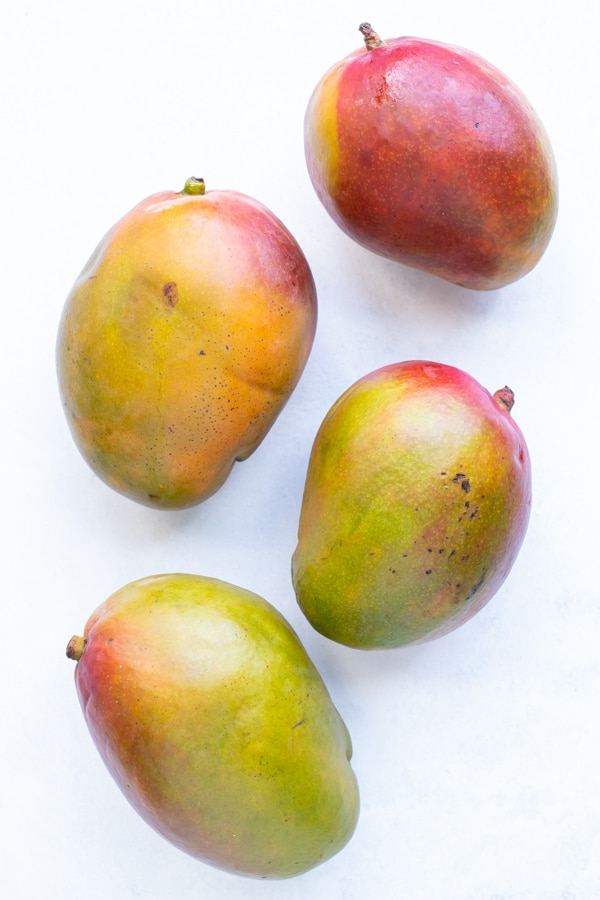 Four ripened mangos with their stems.