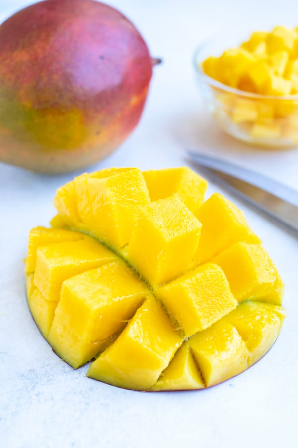 A mango half that has been cut into large chunks.