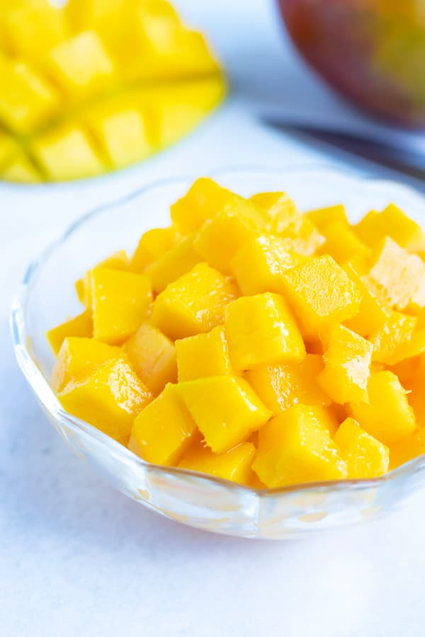 A glass bowl full of cut and diced mango.