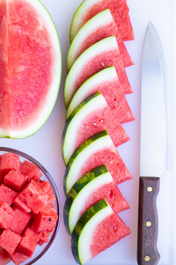 Watermelon wedges in a row on a cutting board next to a knife.