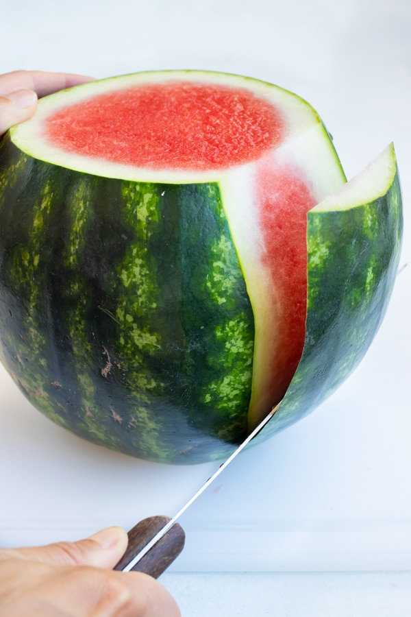 Cutting the rind off of a watermelon between the pink flesh and white part.