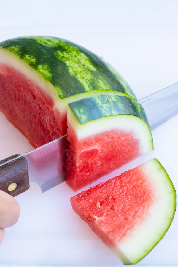 Cutting a slice of watermelon into a wedge.