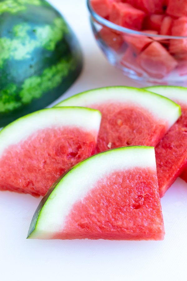 A pile of watermelon slices with a full melon in the background.