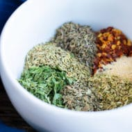 A white bowl full of dried oregano, basil, parsley, rosemary, thyme, and garlic powder for an Italian seasoning recipe.