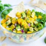 Quick, easy, and fresh mango avocado salsa recipe with a tortilla chip.