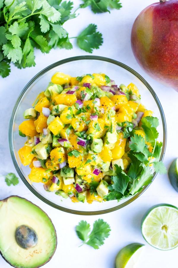 A big bowl of fresh mango salsa with avocado and cilantro.