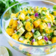 A bowl full of mango salsa with chunks of avocado, cilantro, red onion, and lime juice.