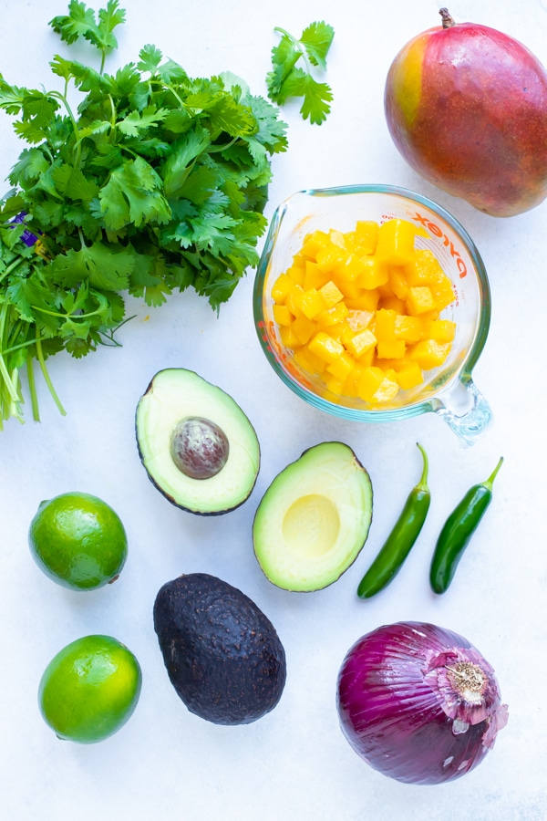 Fresh mango, avocado, serrano peppers, limes, red onion, and cilantro as the ingredients needed for a salsa recipe.