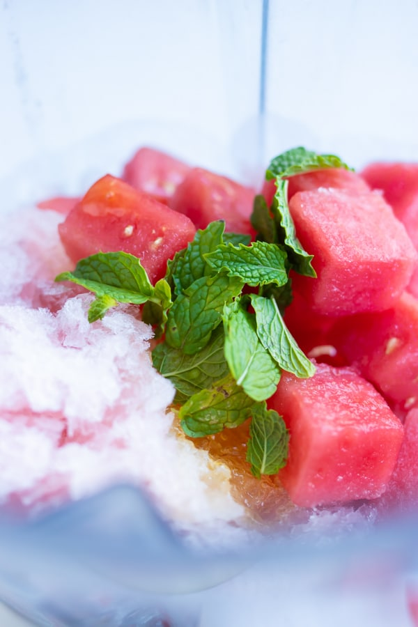 Watermelon cubes, frozen wine, and mint leaves in a blender.