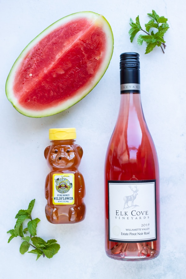 Rose wine, watermelon, honey, and mint as the ingredients needed for a frosé recipe.