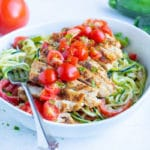 Cajun chicken zoodles in a bowl are topped with sliced fresh tomatoes for an easy, low carb meal.