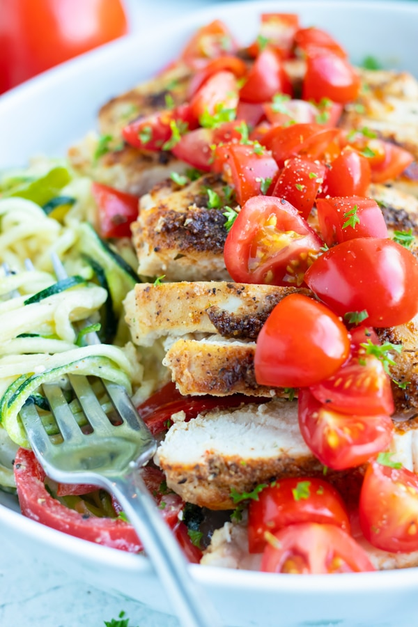 Sliced cajun chicken, tender vegetable noodles, topped with chopped tomatoes are in a bowl for an easy main dish.
