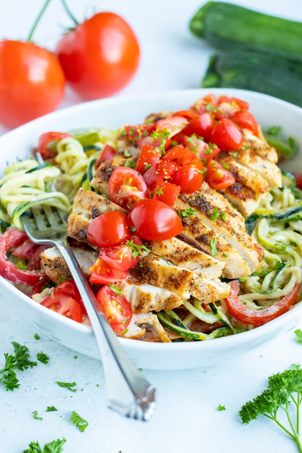 Cajun chicken zoodles in a bowl are topped with fresh tomatoes and parsley for a low-carb and Whole30 meal.