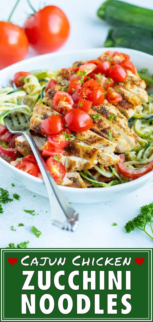 A fork holds spiralized zucchini noodles, covered in a dairy-free alfredo sauce with cajun chicken, fresh tomatoes and sauteéd bell peppers and onions for a gluten-free pasta dish.