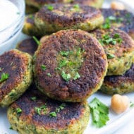 Vegan homemade falafel with fresh parsley and chickpeas are plated with a greek yogurt sauce.
