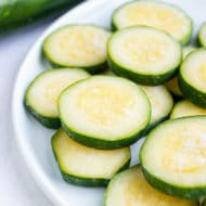 Summer squash that has been previously frozen is now stacked on a plate in preparation for a future recipe.