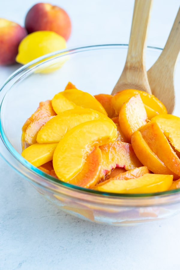 Sliced peaches are placed in a glass bowl as lemon juice is added to prevent browning.