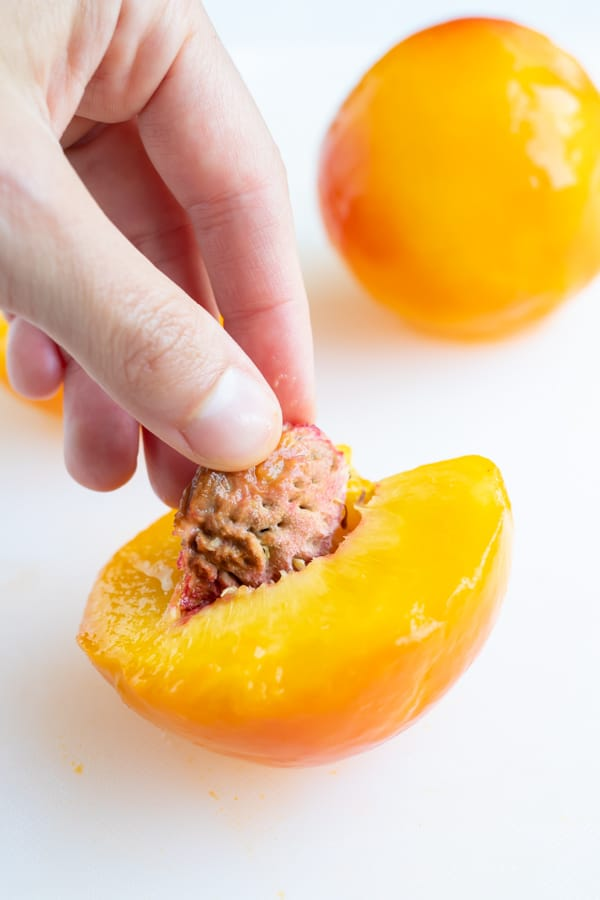 Using your fingers, remove the pit from one side of the peeled peach.