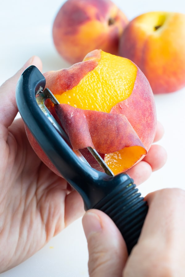 Peeling fruit with a vegetable peeler while two more peaches sit on the counter to be peeled.