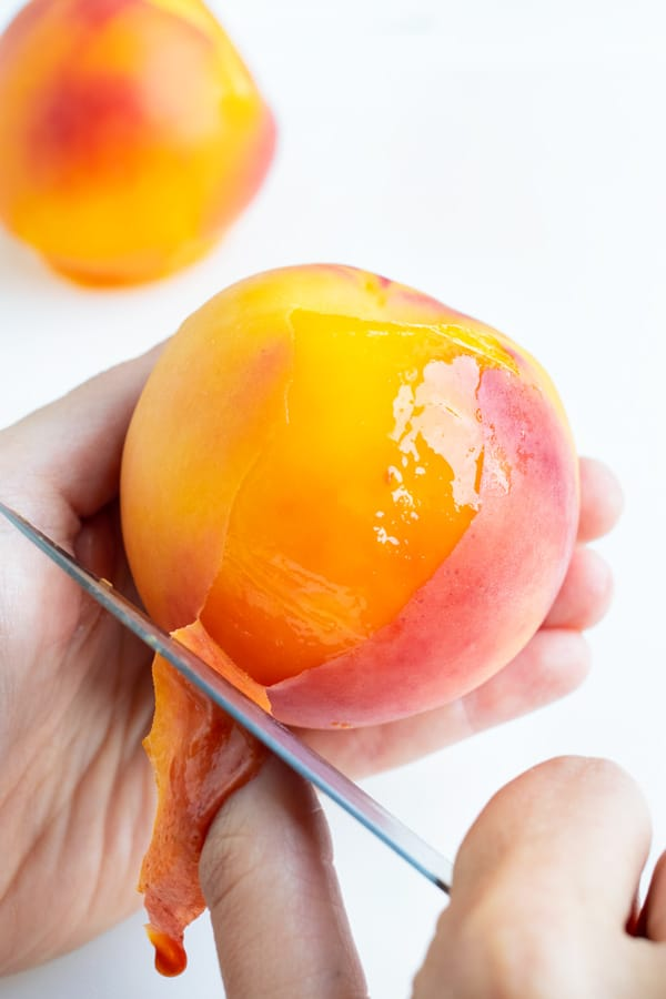 Using a paring knife, peel back the skin of the peach in your hand.