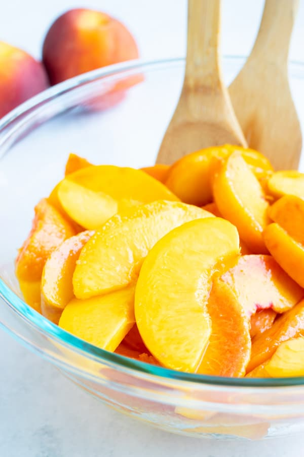 Sliced and peeled peaches are in a glass bowl on the counter with wooden spoons.