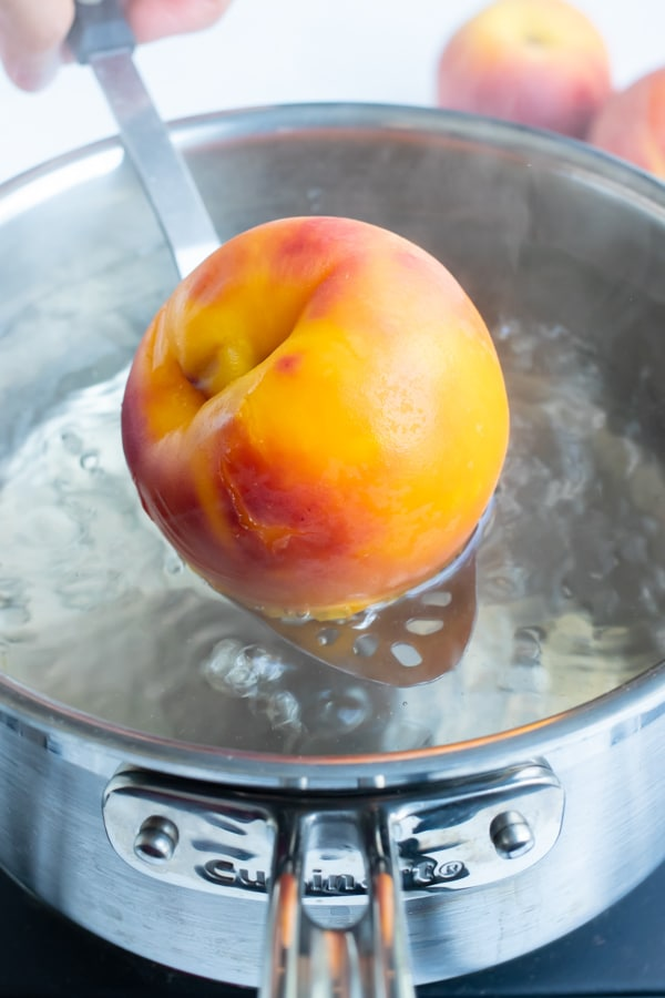 A whole peach is blanched in a pot of hot water and taken out with a metal spoon in preparation for peeling.