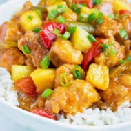 Healthy pressure cooker Pineapple Chicken is loaded with pineapple, bell peppers, and fresh green onions and laid over a rice.