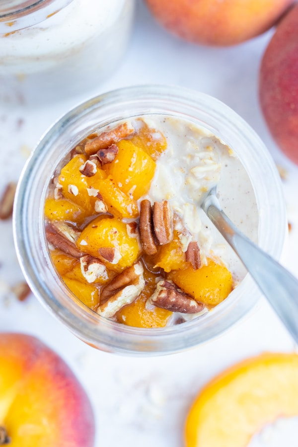Mason jar meal prep oatmeal is made for an easy on-the-go breakfast, snack, or treat made with oats, fresh peaches, and toasted pecans.