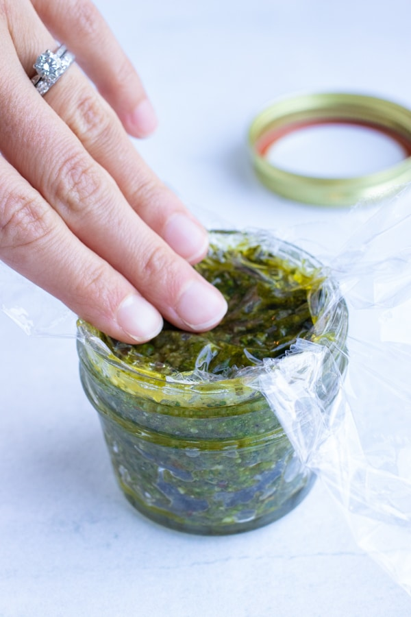 Storing leftover basil pesto in an airtight container covered with a piece of plastic wrap.