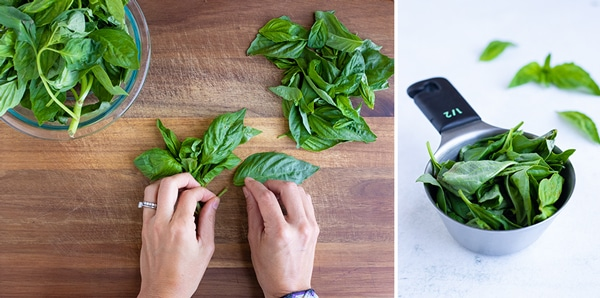 Fresh basil leaves are prepared by snapping the stems off on a wooden cutting board.