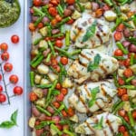 Cooked potatoes, tomatoes, asparagus and baked chicken are on a large baking sheet pan in this easy caprese chicken recipe.