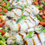 Potatoes are cooked first then followed by tomatoes, chicken, and asparagus in this easy meal prep sheet pan chicken recipe.