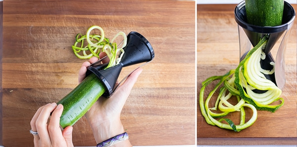 Using a handheld vegetable spiralizer to make zucchini noodles.