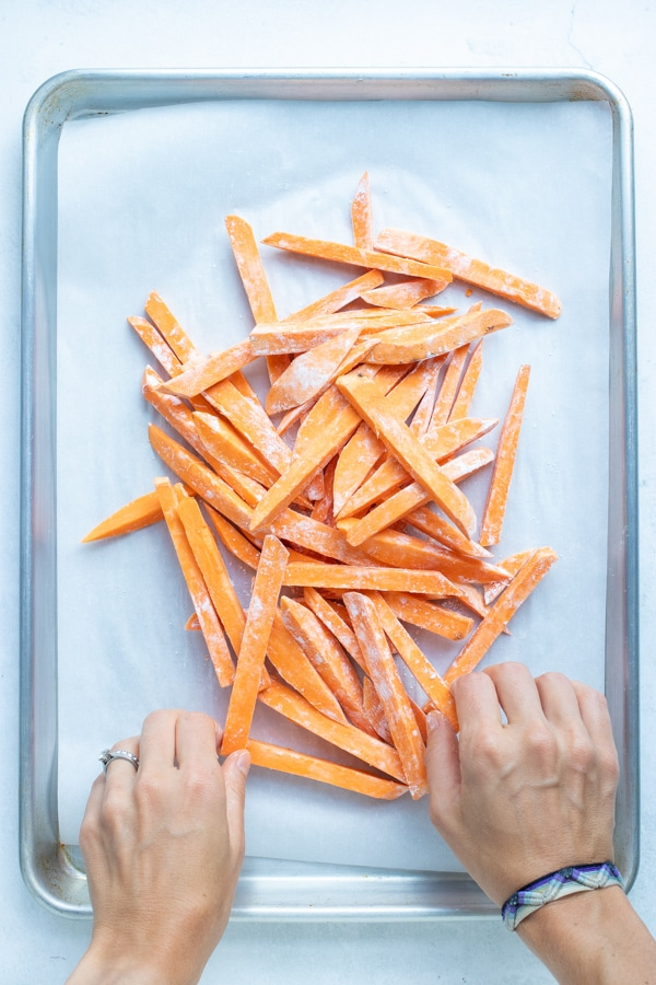 Sweet potato fries that have been tossed in starch on a parchment paper lined baking sheet.