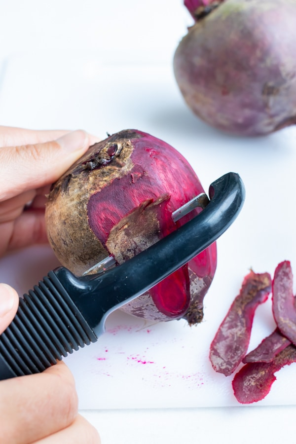Whole beets are peeled with a vegetable peeler before being roasted for this vegan hummus recipe.