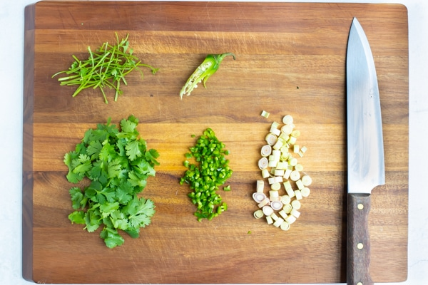Garlic, cilantro, and peppers are chopped and prepared on a cutting board.
