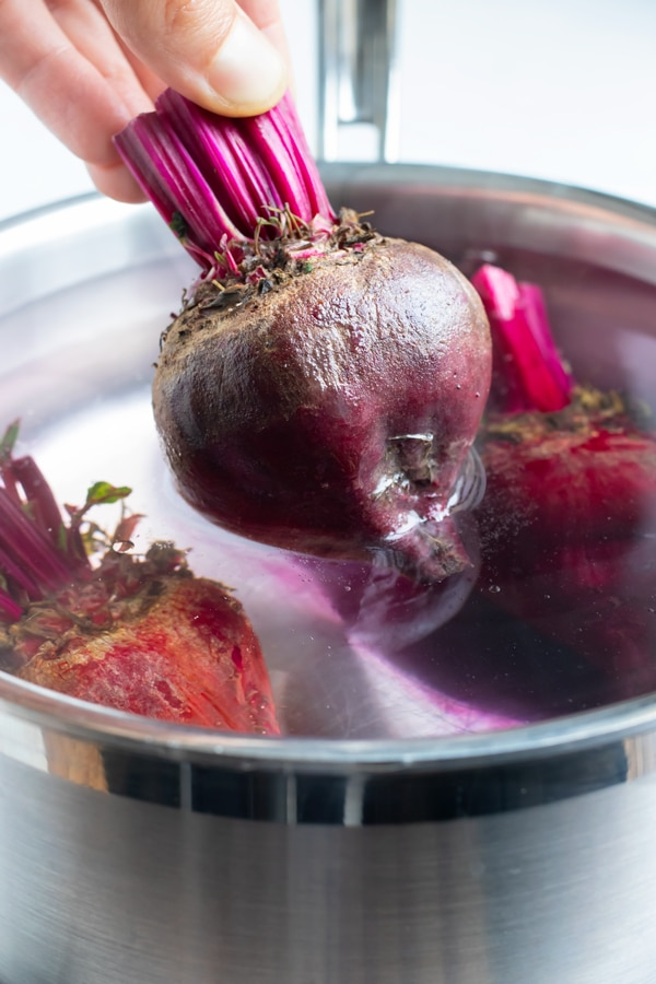 Beets are removed from the pot of water after being boiled.