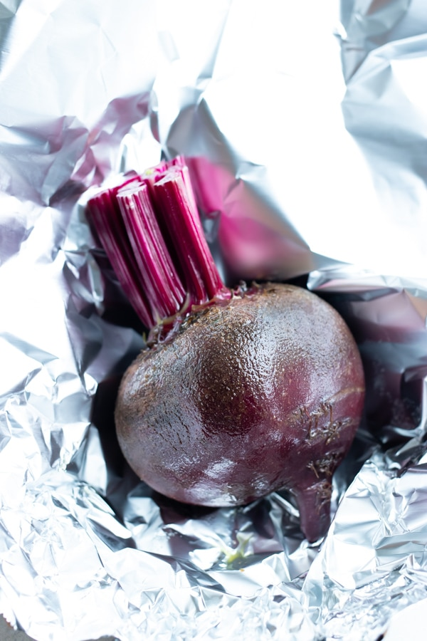 Oil covered beets are wrapped in foil before roasting.