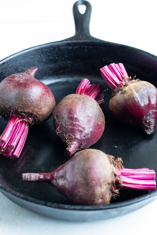 Beets are added to a cast iron skillet and baked in the oven.