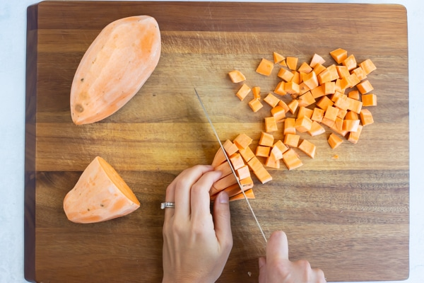 A peeled sweet potato is cut into cubes.