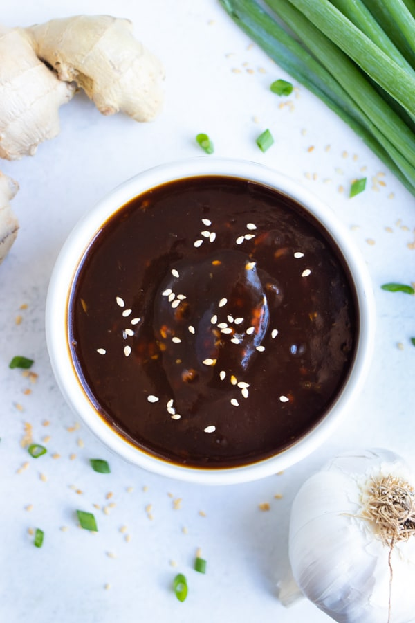 A small bowl full of a sweet and sticky teriyaki sauce to be used as a marinade.