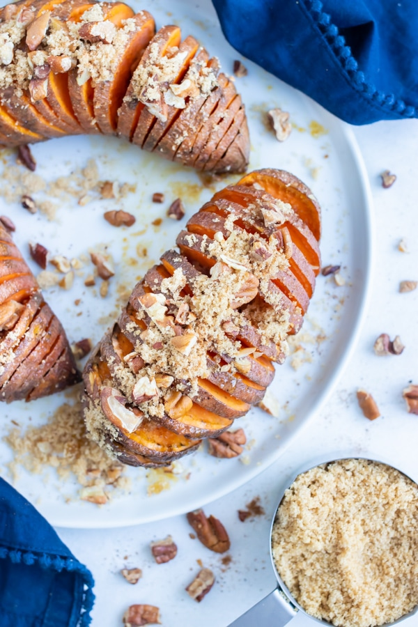 Hasselback sweet potatoes are served with brown sugar, pecans, and cinnamon for a Thanksgiving side dish.