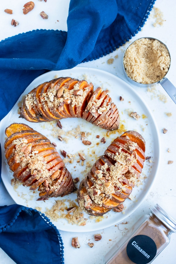 Hasselback Sweet Potatoes are sliced and roasted before being served on a plate.