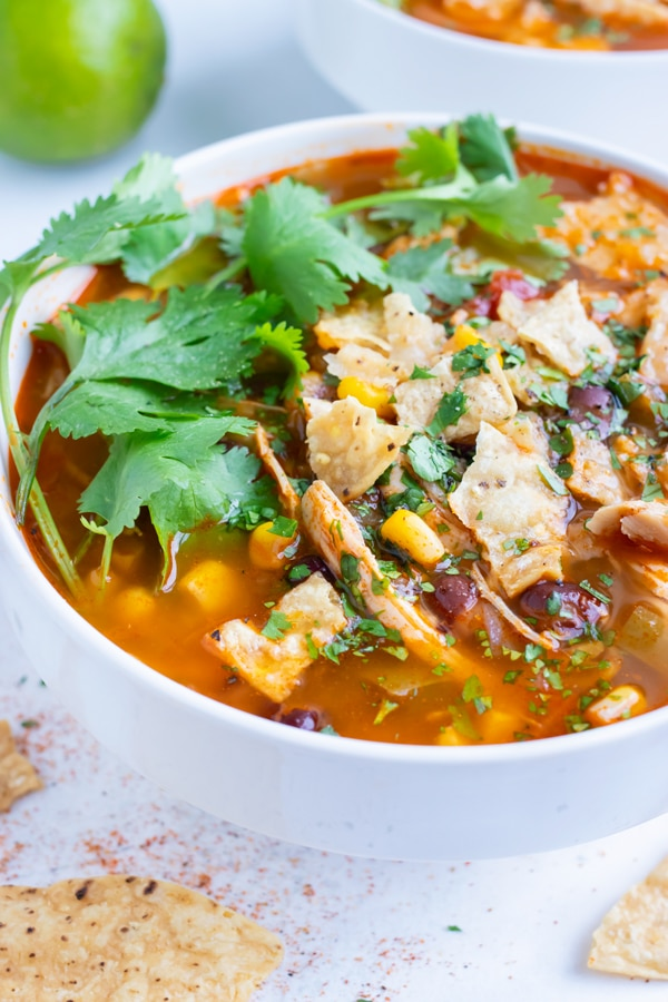 Chicken tortilla soup is placed in a big white bowl and served with fresh lime and tortilla chips.
