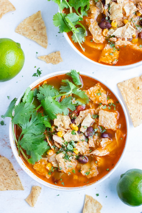 Chicken tortilla soup is topped with cilantro and served in a bowl.