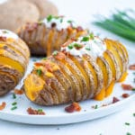Easy stuffed potato side dish is served with bacon, cheese, sour cream.