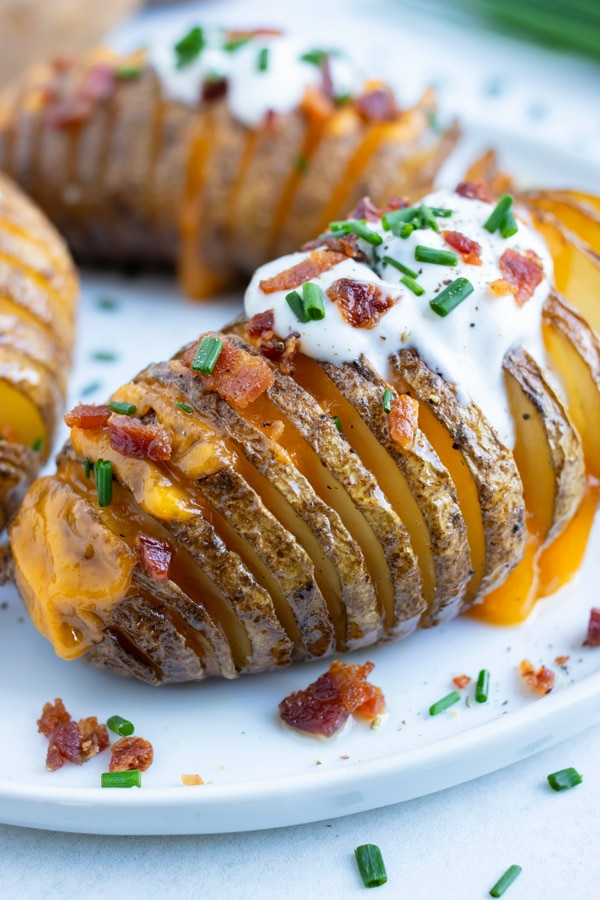 Loaded hasselback potatoes are topped with sour cream and bacon for a Thanksgiving side.