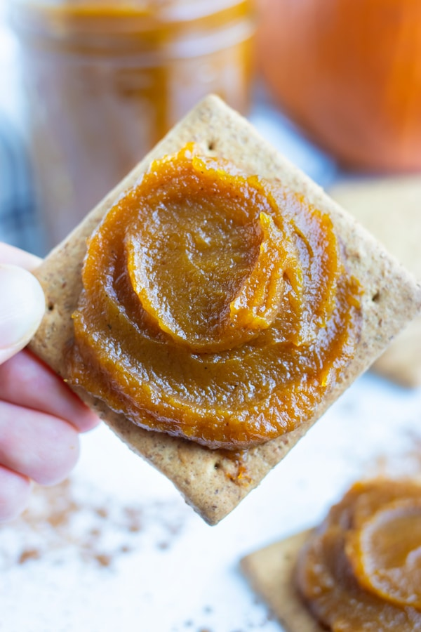 Pumpkin butter is spread on a biscuit for a fall snack.