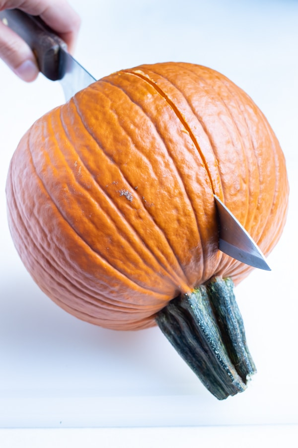 Pumpkin is cut in half with a large knife.